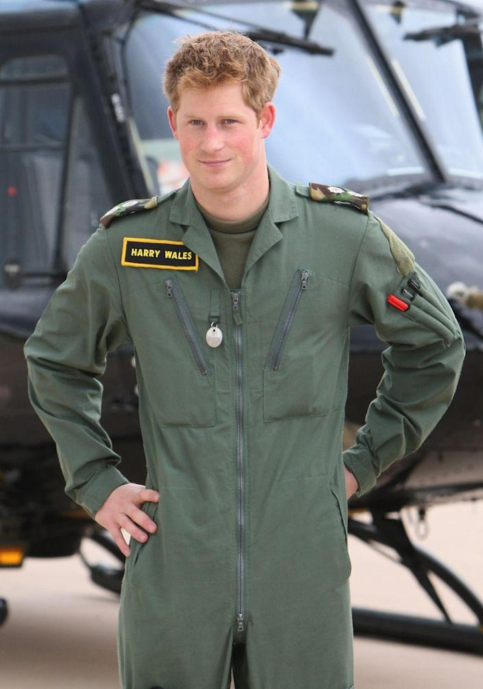<p>Harry poses in front of a helicopter during a photo-call with William (not pictured) at RAF Shawbury. Both princes received their military helicopter training at Shawbury, home of the Defence Helicopter Flying School. </p>