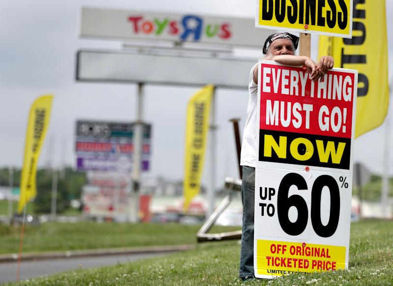 A man holds up a sign announcing the going out of business sale at a Toys R Us and Babies R Us store location, Friday, June 1, 2018, in Totowa, N.J. Politicians, including U.S. Sen. Bob Menendez and Sen. Cory Booker, held a news conference at the Totowa location to voice their concerns after it was announced that employees will not get severance packages once the stores are closed following the bankruptcy of the company. (AP Photo/Julio Cortez)
