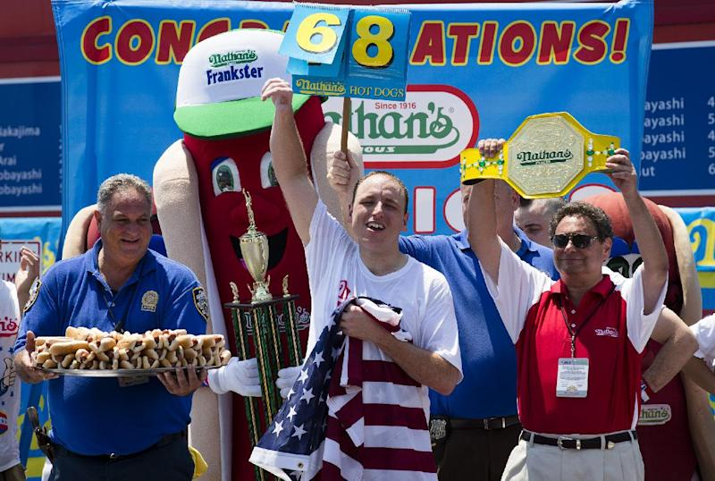 Five-time reigning champion Joey Chestnut celebrates after he wins his sixth straight Coney Island hot dog eating contest on Wednesday, July 4, 2012  at Coney Island, in the Brooklyn borough of New York. Chestnut tied his personal best and the record with eating 68 hot dogs. Last year, Chestnut won with 62 hot dogs. (AP Photo/John Minchillo)