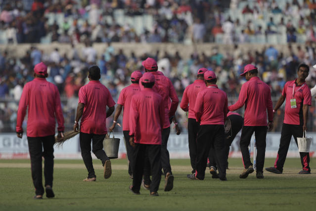Groundsmen wearing pink shirt, commemorating first pink ball match, clear the ground during the first day of the second test match between India and Bangladesh, in Kolkata, India, Friday, Nov. 22, 2019. (AP Photo/Bikas Das)