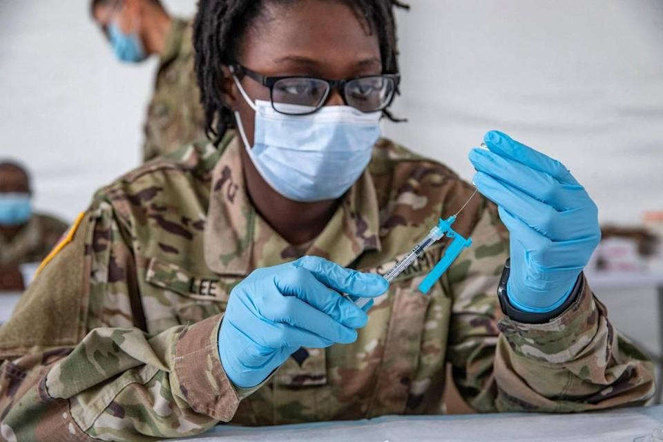 Taeja Lee, 22, a U.S. Army Pharmacy Technician, prepares a COVID-19 vaccine for use during opening day of the FEMA vaccination site on Miami-Dade College's North Campus on Wednesday, March 3, 2021.