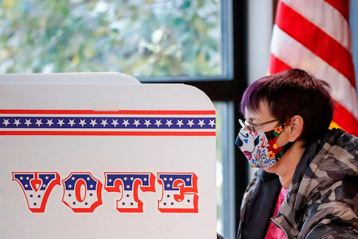 A woman casts her ballot at Tippecanoe Library on the first day of in-person early voting for the November 3rd elections in Milwaukee, Wisconsin, on October 20, 2020.