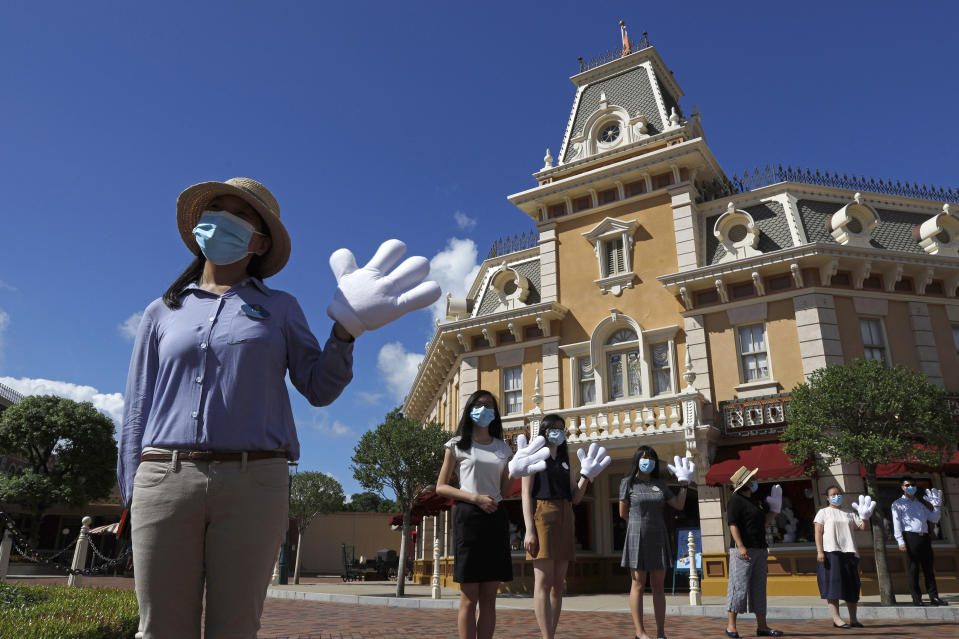 Employees wearing face masks to prevent the spread of the new coronavirus, welcome visitors at the Hong Kong Disneyland on Thursday, June 18, 2020. Hong Kong Disneyland on Thursday opened its doors to visitors for the first time in nearly five months, at a reduced capacity and with social distancing measures in place. The theme park closed temporarily at the end of January due to the coronavirus outbreak, and is the second Disney-themed park to re-open worldwide, after Shanghai Disneyland. (AP Photo/Kin Cheung)