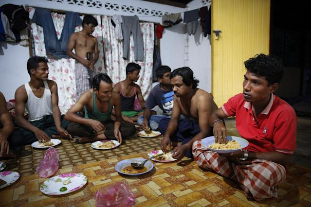In this Nov. 23, 2013 photo, Rohingya refugee Mohamad Husein, right, from Myanmar, eats dinner at his hostel with his compatriots on the outskirts of Alor Setar, Kedah, North Malaysia. For many fleeing Rohingya, Malaysia, is the preferred destination. Around 33,000 are registered there and an equal number are undocumented, according to the Rohingya Society of Malaysia. Those numbers have swelled with the violence in Myanmar. (AP Photo/Vincent Thian)