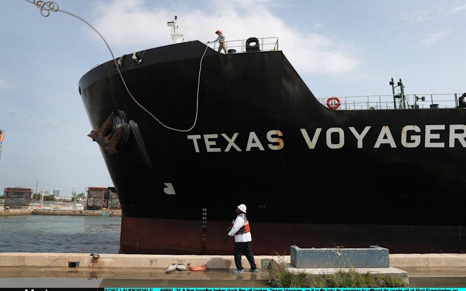 A line handler helps dock the oil tanker, Texas Voyager, as it pulls into its mooring to offload its crude oil at Port Everglades - Joe Raedle/Getty Images