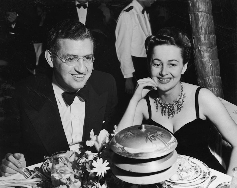 <p>Olivia wearing a dark evening dress with a diamond necklace to a dinner party in 1935.</p>