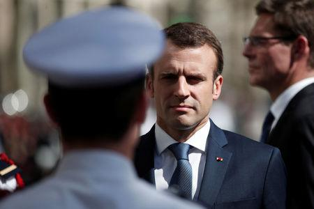 French President Emmanuel Macron attends a ceremony to pay tribute to Xavier Jugele one year after the French police officer was killed during a shooting incident, on the Champs Elysees avenue in Paris