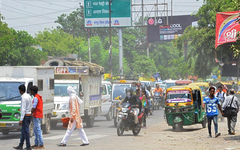Pedestrians and vehicles jostle for space in Kanpur, India - AFP
