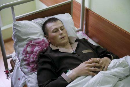 A man, according to Ukraine's state security service one of two Russian servicemen recently detained by Ukrainian forces, lies on a bed at a hospital in Kiev