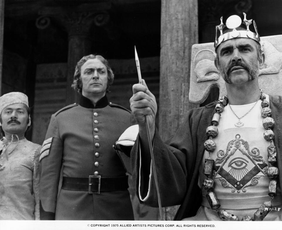 Michael Caine standing behind Sean Connery in a scene from the film 'The Man Who Would Be King', 1975. (Photo by Columbia/Getty Images)