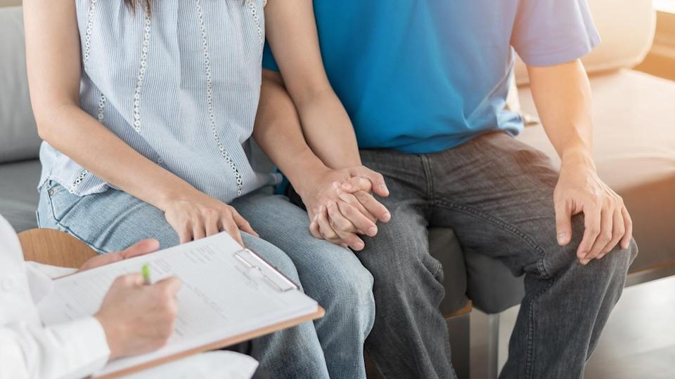 Patient couple consulting with doctor