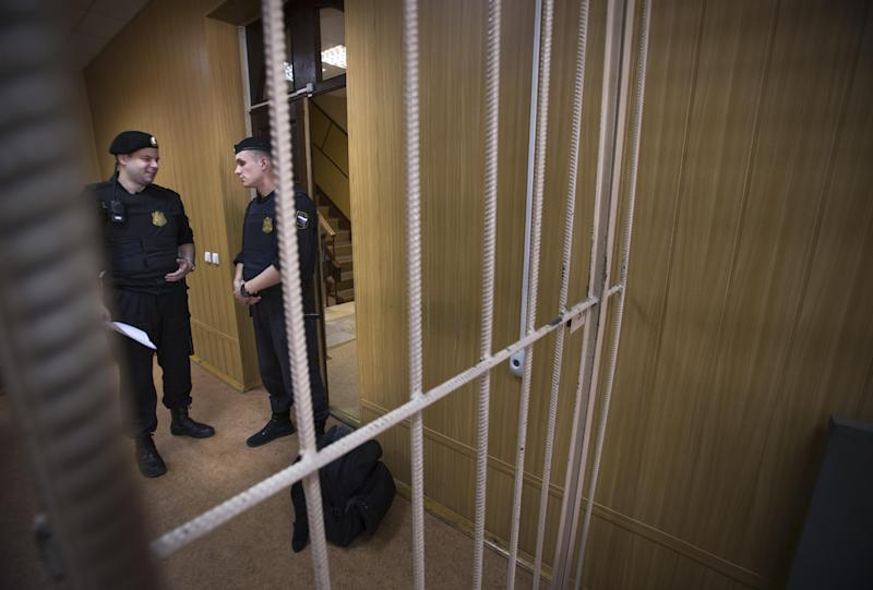 Bailiffs stand near a cage in a courtroom in Moscow, Russia, Thursday, 11, 2013. Russian news agencies say a court in Moscow has found dead lawyer Sergei Magnitsky guilty of tax evasion, concluding an unusual posthumous trial. Magnitsky died in prison of untreated pancreatitis in 2009, months after alleging that organized criminals colluded with corrupt Interior Ministry officials to claim a $230 million tax rebate through illegally obtained subsidiaries of Browder's Hermitage Capital investment company. (AP Photo/Alexander Zemlianichenko)