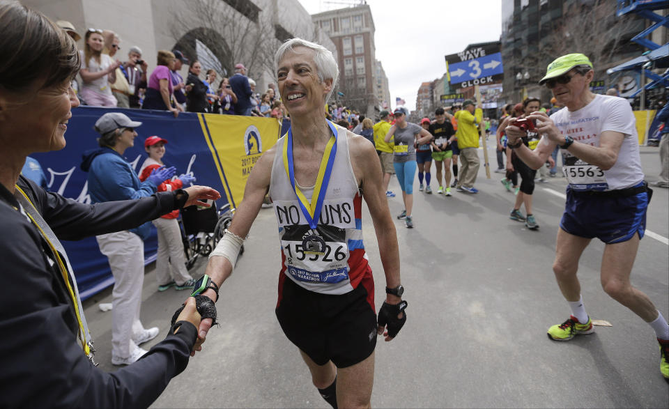 FILE - In this April 17, 2017, file photo, three-time Boston Marathon winner Uta Pipping, left, congratulates Ben Beach, of Bethesda, Md., after he finished running his 50th consecutive Boston Marathon in Boston. Ben Beach has experienced a little bit of everything while running in a record 53 consecutive Boston Marathons — from New England's unpredictable weather to a diagnosis with dystonia to the 2013 bombing to last year's pandemic disruption. (AP Photo/Elise Amendola, File)