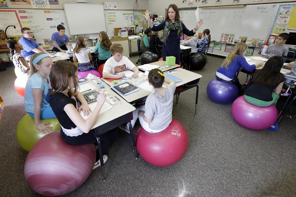 """Robbi Giuliano teaches her fifth grade class as they sit on yoga balls at Westtown-Thornbury Elementary School Monday, Feb. 4, 2013, in West Chester, Pa. Giuliano says """"I'm able to get a lot done with them because they're sitting on yoga balls."""" (AP Photo/Matt Rourke)"""