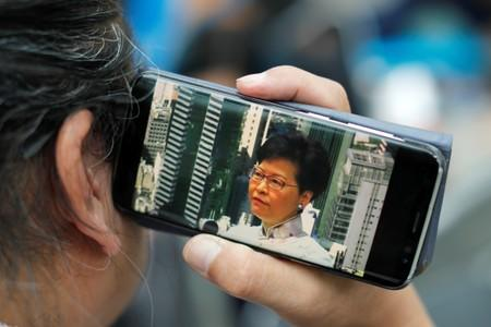A man uses mobile phone to listen to a news conference, as people gather to wait for a government announcement regarding the proposed extradition bill, near the Legislative Council building in Hong Kong