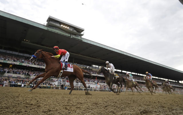 Justify (1), with jockey Mike Smith up, crosses the finish line to win the 150th running of the Belmont Stakes horse race, Saturday, June 9, 2018, in Elmont, N.Y. (AP Photo/Julio Cortez)