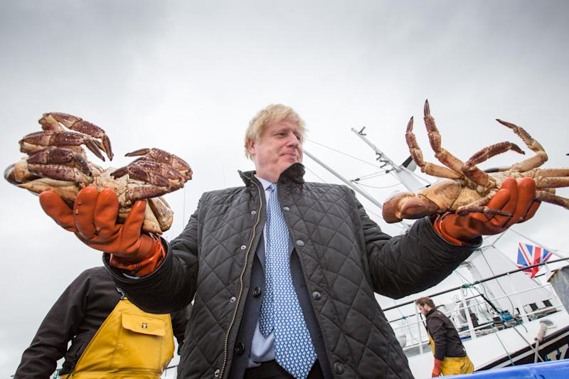 STROMNESS, SCOTLAND - JULY 23: British Prime Minister Boris Johnson holds crabs caught on the Carvela at Stromness Harbour on July 23, 2020 in Stromness, Scotland. This week marks one year as U.K. Prime Minister for Conservative Party leader Boris Johnson. Today he is visiting businesses in the Orkney Islands in Scotland to reaffirm his commitment to supporting all parts of the UK through the Coronavirus pandemic. Later he will visit a military base in Moray to thank Military personnel for their service. (Photo by Robert Perry - WPA Pool/Getty Images)