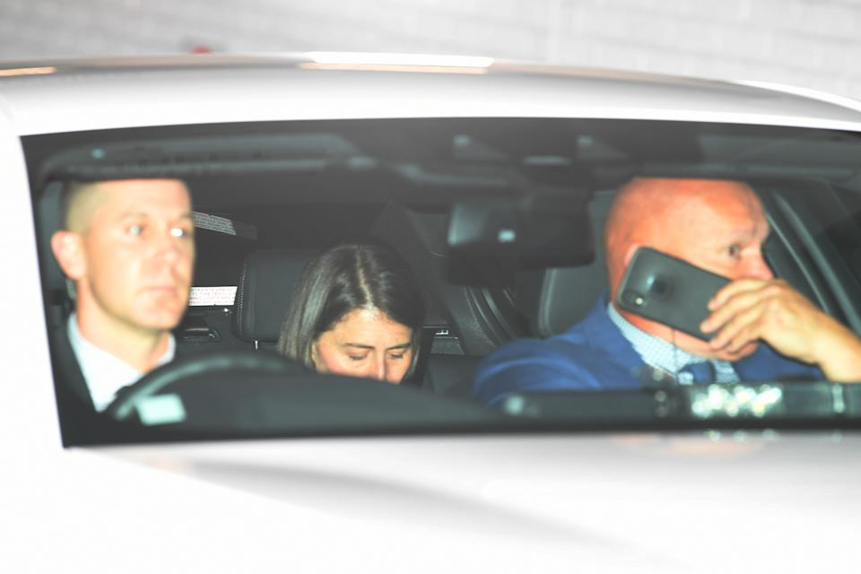 Premier Gladys Berejiklian dips her head down in the backseat of a car after giving evidence to the ICAC.