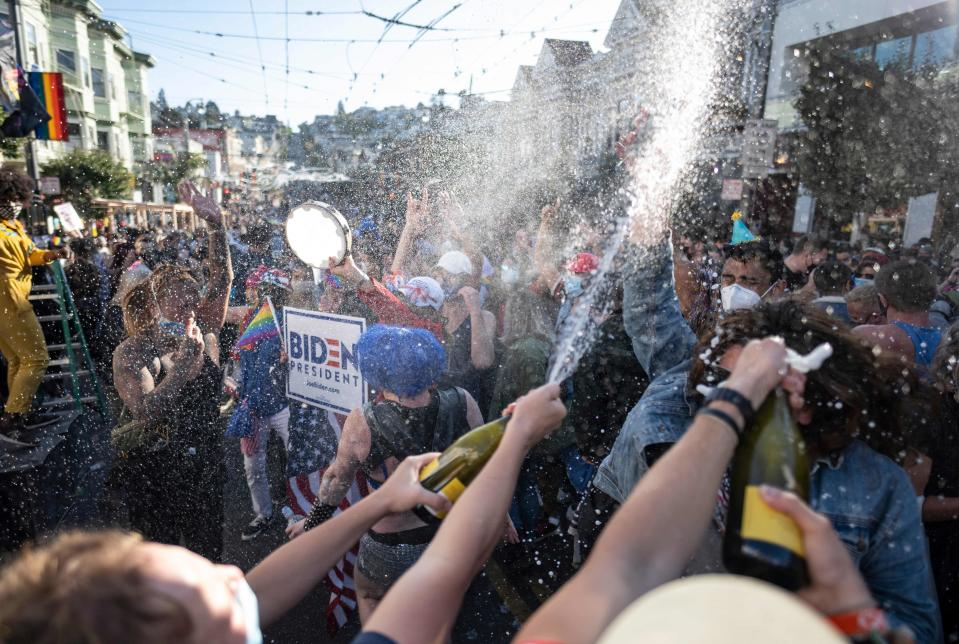 People spray champagne as they celebrate Joe Biden being elected President of the United States in the Castro district of San Francisco, California on November 7, 2020. - Democrat Joe Biden has won the White House, US media said November 7, defeating Donald Trump and ending a presidency that convulsed American politics, shocked the world and left the United States more divided than at any time in decades. (Photo by JOSH EDELSON / AFP) (Photo by JOSH EDELSON/AFP via Getty Images)