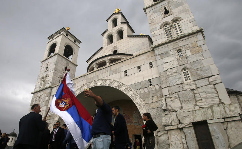 """In this Saturday, Oct. 15, 2016 file photo, a man holds Serbian flag during a wedding ceremony in front of the Serbian Orthodox Church of Christ's Resurrection in Podgorica, Montenegro. A Serb official has branded Montenegro a """"criminal"""" state and threatened a """"fierce"""" response over the neighboring country's plans to introduce a church law. The draft law calls for all religious communities in Montenegro to provide proof that they owned their property before 1918 when the small Adriatic state lost its independence and became part of the Serb-dominated Kingdom of Serbs, Croats and Slovenes. If they don't, the property becomes state owned. (AP Photo/Darko Vojinovic, File)"""
