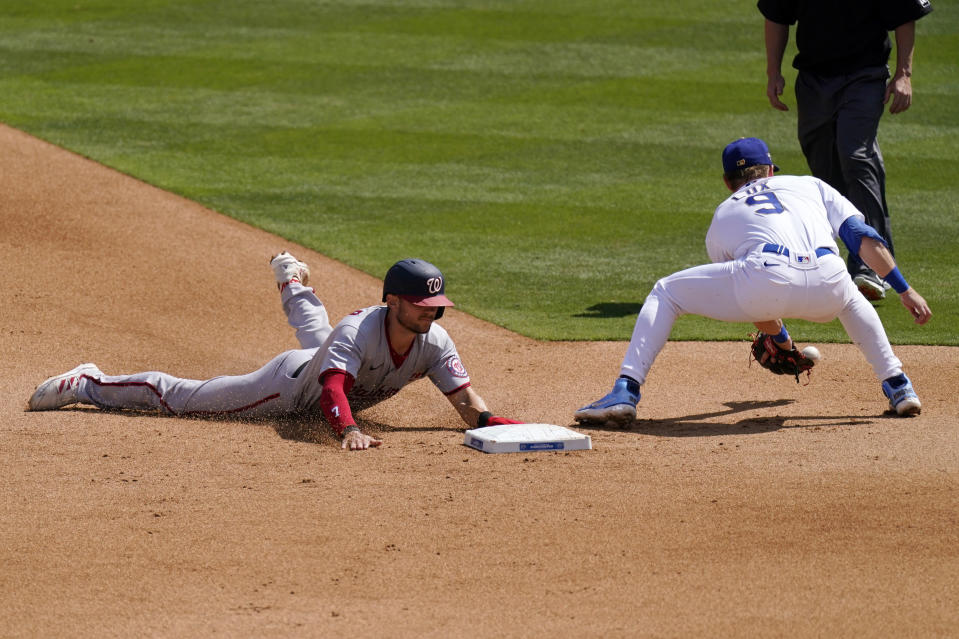Washington Nationals' Trea Turner, left, dives into second on a wild pitch as Los Angeles Dodgers second baseman Gavin Lux takes a late throw from home during the sixth inning of a baseball game Sunday, April 11, 2021, in Los Angeles. (AP Photo/Mark J. Terrill)