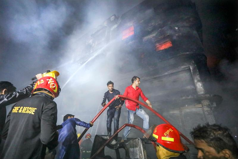locals and firefighters douse flames of a smoldering fire in a building in Dhaka, Bangladesh, Feb. 21, 2019. (Photo: AP)