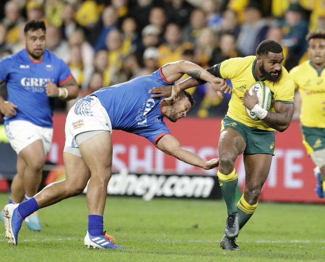 Australia's Marika Koroibete, right, breaks the tackle of Samoa's Alapati Leiua on his way to scoring a try during their rugby union test match in Sydney, Saturday, Sept. 7, 2019. (AP Photo/Rick Rycroft)