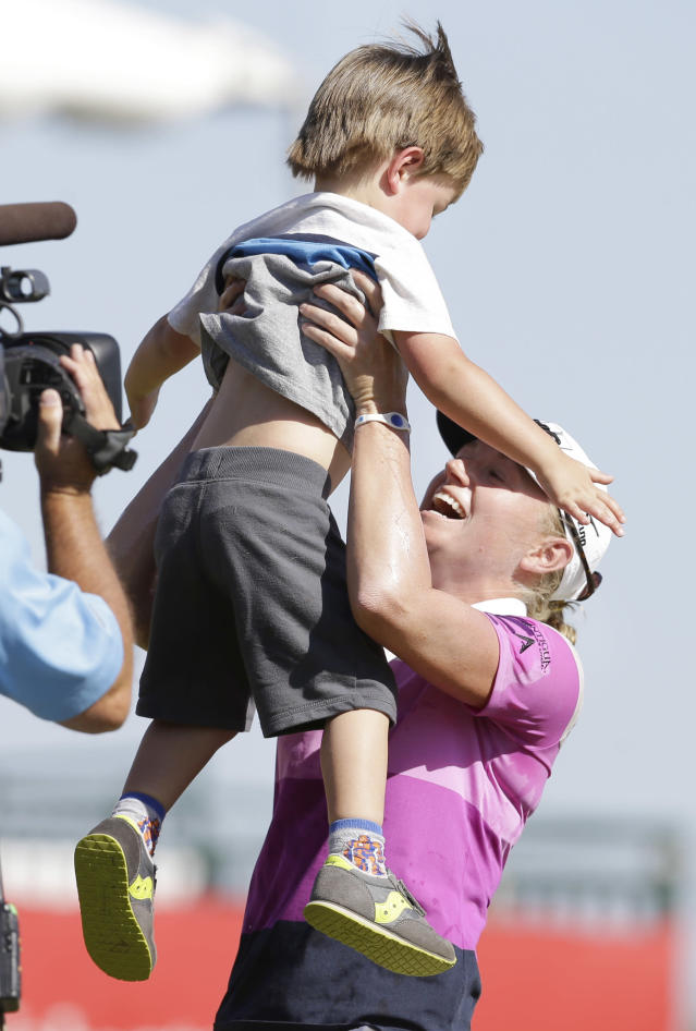 Stacey Lewis lifts her nephew Cole Wysocki, 3, after winning the North Texas LPGA Shootout golf tournament at Las Colinas Country Club in Irving, Texas, Sunday, May 4, 2014. (AP Photo/LM Otero)