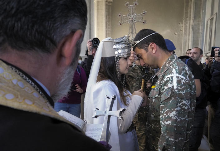 Newlyweds, soldier Hovhannes Hovsepyan, right, and Mariam Sargsyan get married in the Holy Savior Cathedral, damaged by shelling by Azerbaijan's artillery during a military conflict in Shushi, the separatist region of Nagorno-Karabakh, Saturday, Oct. 24, 2020. The wedding was celebrated even as intense fighting in the region has continued. (AP Photo)