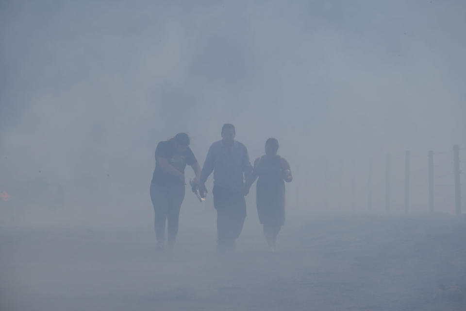 Jose Lamas, center, his wife, Maria Covarrubias, right, and their daughter, Astrid, walk through smoke-filled air after visiting their home burned by the South Fire in Lytle Creek, San Bernardino County, north of Rialto, Calif., Wednesday, Aug. 25, 2021. (AP Photo/Ringo H.W. Chiu)