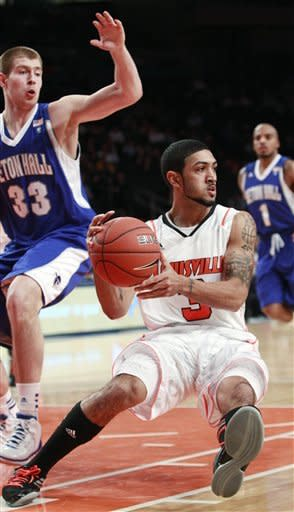 Louisville's Peyton Siva (3) passes away from Seton Hall's Patrik Auda (33) as Jordan Theodore (1) watches in the first half of a second-round NCAA college basketball game at the Big East tournament in New York, Wednesday, March 7, 2012. (AP Photo/Frank Franklin II)