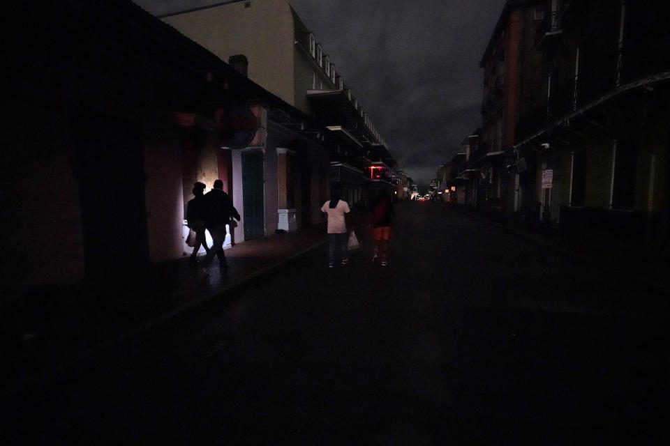 A darkened Bourbon Street is illuminated only by passers-by with lights and car headlights in the French Quarter in New Orleans, Wednesday, Oct. 28, 2020. Hurricane Zeta passed through today leaving much of the city and metro area without power. (AP Photo/Gerald Herbert)