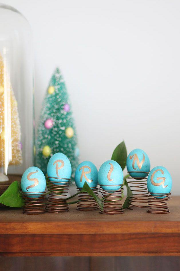 """<p>This cheeky DIY — spelling out """"spring"""" on eggs atop actual <em>springs </em>— is a silly and fun way to bring Easter cheer to your home. Using robin's egg colored paint invokes the sense of nature coming alive after a long winter.</p><p><em><a href=""""http://www.abeautifulmess.com/2014/04/spring-easter-egg-display.html"""" rel=""""nofollow noopener"""" target=""""_blank"""" data-ylk=""""slk:Get the tutorial at A Beautiful Mess »"""" class=""""link rapid-noclick-resp"""">Get the tutorial at A Beautiful Mess »</a></em><br></p><p><a class=""""link rapid-noclick-resp"""" href=""""https://www.amazon.com/Beadsmith-12-Gauge-Aluminum-39-Feet-Copper/dp/B00J3MK3GW/?tag=syn-yahoo-20&ascsubtag=%5Bartid%7C10055.g.2217%5Bsrc%7Cyahoo-us"""" rel=""""nofollow noopener"""" target=""""_blank"""" data-ylk=""""slk:BUY WIRE"""">BUY WIRE</a></p>"""