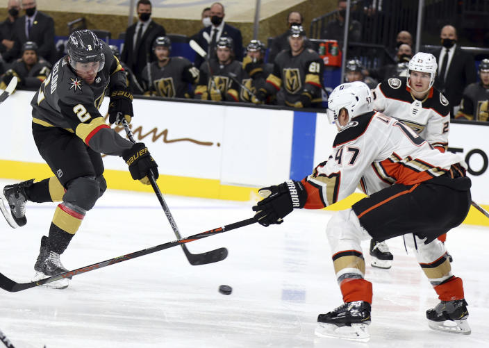 Vegas Golden Knights defenseman Zach Whitecloud (2) shoots as Anaheim Ducks' Hampus Lindholm (47) defends during the second period of an NHL hockey game Thursday, Jan. 14, 2021, in Las Vegas. (AP Photo/Isaac Brekken)
