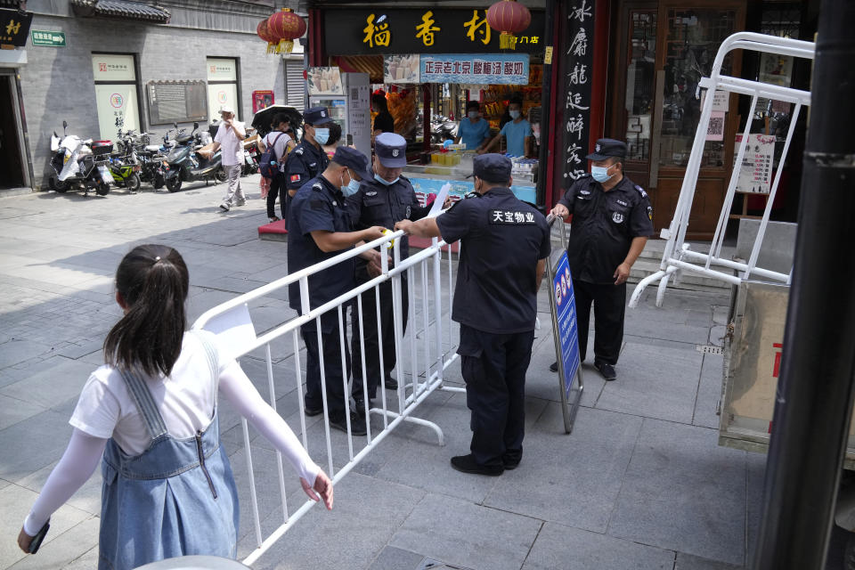 Security officers put up access control barriers along a pedestrian shopping street in a neighborhood popular with tourists in central Beijing, Tuesday, Aug. 3, 2021. From the Great Wall to the picturesque Kashmir valley, Asia's tourist destinations are looking to domestic visitors to get them through the COVID-19 pandemic's second year. With international travel heavily restricted, foreign tourists can't enter many countries and locals can't get out. (AP Photo/Mark Schiefelbein)