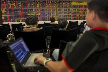 Thai investors sit in front of an electronic board displaying live market data at a stock broker's office in central Bangkok, Thailand, August 24, 2015. REUTERS/Athit Perawongmetha/Files