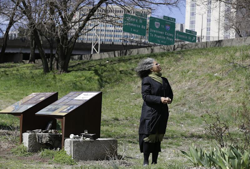 Ana Edwards, the chief opponent of the Shockoe Bottom stadium proposal looks up at some of the trees in the area in front of historical markers at the Slave Burial Ground in Richmond, Va., Monday, March 31, 2014. A proposal to build a minor league baseball stadium in Shockoe Bottom, the city's oldest neighborhood and the center of the once-thriving slave trade, has drawn criticism from some who believe the area is sacred ground and shouldn't be bulldozed for a ballpark. The city says it will recover and display artifacts related to the slave trade.(AP Photo/Steve Helber)