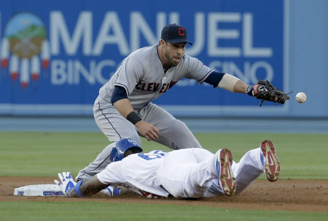 Cleveland Indians second baseman Jason Kipnis, top, fails to catch the throw as Los Angeles Dodgers' Yasiel Puig slides into second base for a double during the first inning of a baseball game in Los Angeles, Tuesday, July 1, 2014. (AP Photo/Chris Carlson)