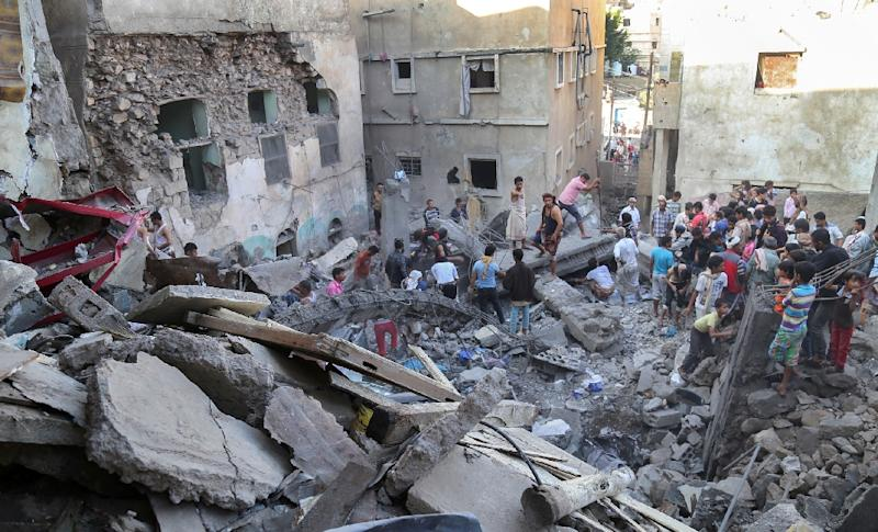 Residents inspect the debris of a building that collapsed during a reported Saudi-led coalition air strike against Shiite Huthi rebels and their allies in Taez, Yemen's third largest city, on November 1, 2015