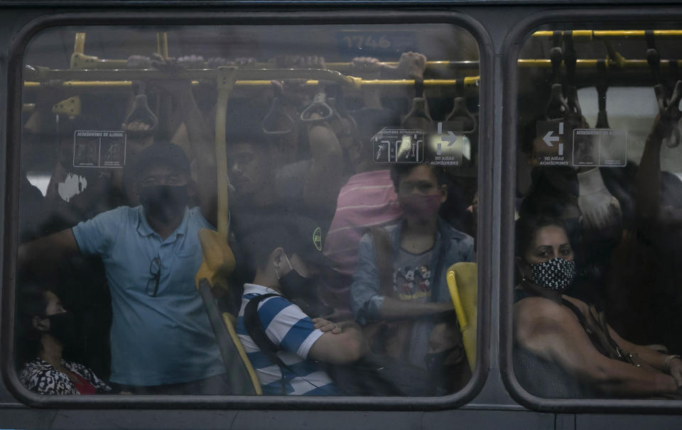 Commuters wearing masks due to the COVID-19 pandemic crowd a public Rapid Transit Bus (BRT) in Rio de Janeiro, Brazil, Tuesday, March 30, 2021. (AP Photo/Bruna Prado)