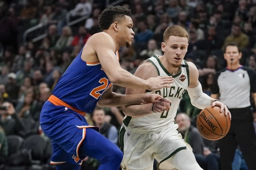 Milwaukee Bucks' Donte DiVincenzo drives past New York Knicks' Kevin Knox II during the second half of an NBA basketball game Tuesday, Jan. 14, 2020, in Milwaukee. (AP Photo/Morry Gash)