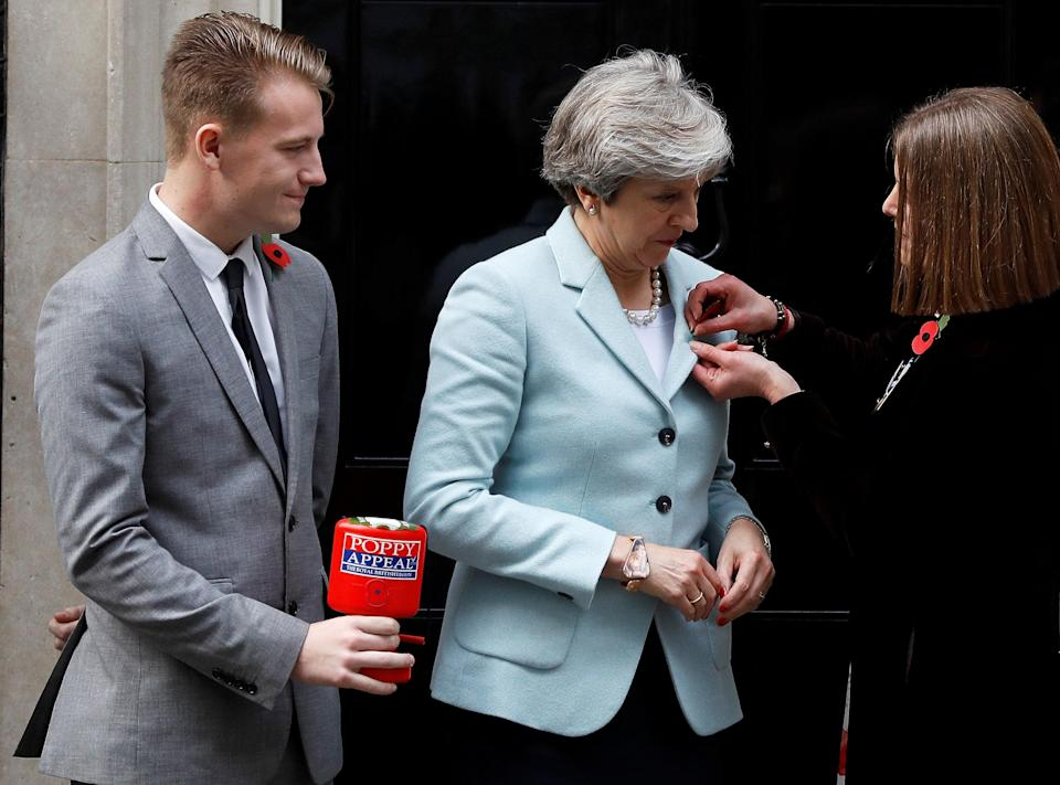 British Legion fundraiser Claire Rowcliffe pins a poppy on to Britain's Prime Minister Theresa May, as her colleague George Taylor looks on outside 10 Downing Street in London, October 30, 2017. (Picture: REUTERS/Peter Nicholls)