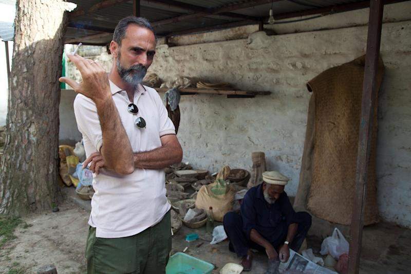 In this May 24, 2012 photo, Italian archeologist Luca Olivieri, left, talks with colleagues in Saidu Sharif, Pakistan. Olivieri and his partners are working to restore a carving of the Buddha destroyed by Taliban fighters in Pakistan's Swat valley. (AP Photo/B.K. Bangash)