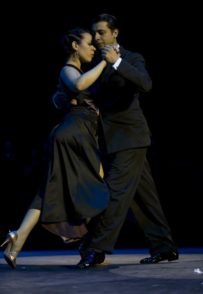 Argentina's couple Facundo de la Cruz Gomez Palavecino, right, and Paola Sanz dance after winning the 2012 Tango Dance World Cup salon finals in Buenos Aires, Argentina, Monday, Aug. 27, 2012. Couples from around the world competed in the finals Argentina's annual tango competition, the highlight of a two-week festival which this year honored Astor Piazzolla, the legendary composer and bandoneonista who revived the genre and infuriated purists by blending tango with rock music in the 1970s. (AP Photo/Natacha Pisarenko)
