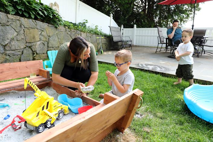 Diane Segel and her 3-year-old son William with special needs play with the sandbox toys as her 1-year-old son Charlie and husband Will Segel look on at home in Thornwood, N.Y. She started a petition to open up an extended school year for kids with special needs and over 25,000 people have signed it. She's been struggling over the last three months as online education doesn't work for her son and feels that he needs his in-person services to continue to develop.