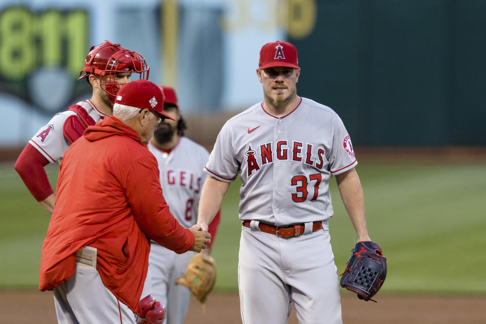 Los Angeles Angels starting pitcher Dylan Bundy (37) is relieved by manager Joe Maddon, left front, during the third inning of a baseball game against the Oakland Athletics in Oakland, Calif., Monday, June 14, 2021. (AP Photo/John Hefti)