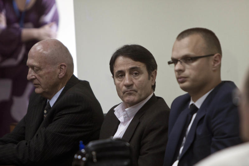 Kosovo Albanian doctor Lutfi Dervishi, center, flanked by defense councils, sits in a court room, in Pristina, Kosovo, Monday, April 29, 2013. A Kosovo court has found two ethnic Albanians guilty of human trafficking and organized crime in a highly publicized trial against seven people suspected of running an international organ trafficking ring. A panel of two European Union and one Kosovo judges sentenced Lutfi Dervishi to eight years in prison and his son Arban Dervishi to seven years and three months in prison on Monday for extracting kidneys from poor donors who were lured by financial promises. ( AP Photo/Visar Kryeziu)
