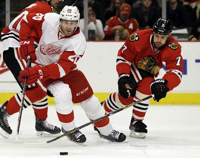 Detroit Red Wings' Drew Miller, left, controls the puck against Chicago Blackhawks' Brent Seabrook (7) during the first period of an NHL hockey game in Chicago, Sunday, March 16, 2014. (AP Photo/Nam Y. Huh)