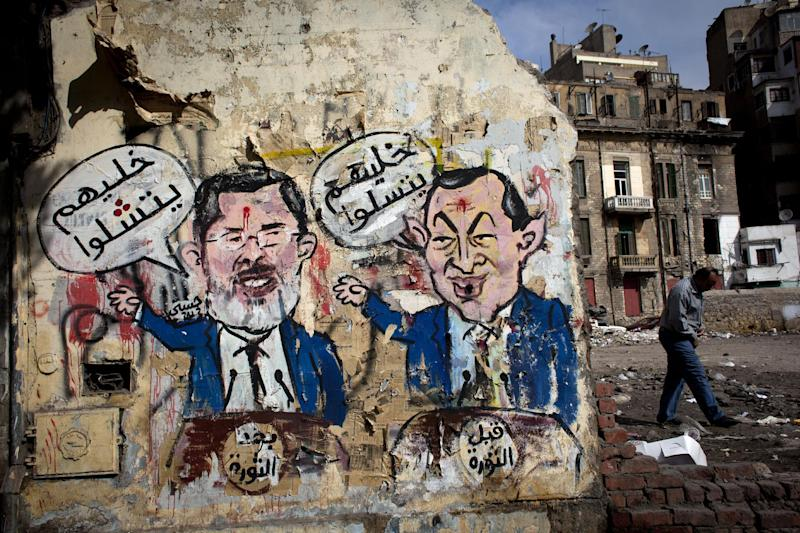 "An Egyptian man walks by a mural depicting ousted president Hosni Mubarak, right, and Egyptian President Mohammed Morsi, left, with Arabic that reads ""before the revolution, let them be amused, after the revolution, let them be paralyzed,"" on a wall in Tahrir Square, Cairo, Egypt, Tuesday, Feb. 19, 2013. An ultraconservative Islamist adviser to Egypt's president resigned yesterday in solidarity with a fellow aide who was fired amid allegations of abuse of office. (AP Photo/Nasser Nasser)"