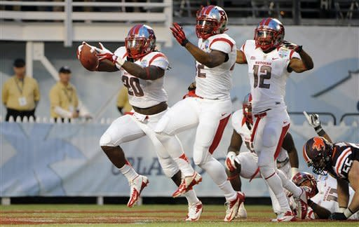 Rutgers linebacker Khaseem Greene, left, celebrates with linebacker Steve Beauharnais, center, and defensive back Marcus Cooper (12) after recovering a fumble in the end zone for a touchdown during the first quarter of the NCAA college football Russell Athletic Bowl game against Virginia Tech, Friday, Dec. 28, 2012, in Orlando, Fla. (AP Photo/Brian Blanco)